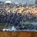 FILE PHOTO:  Israeli soldiers shoot tear gas from the Israeli side of the Israel-Gaza border, as Palestinians protest on the Gaza side of the border